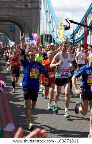 LONDON, UK - APR. 22: Tens of thousands of people pass Tower Bridge during the London Marathon on the Apr 22, 2012 in London, UK - stock photo