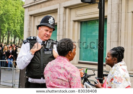 LONDON, UK - APRIL 29: A policeman talking to people at Prince William and Kate Middleton wedding, April 29, 2011 in London, United Kingdom - stock photo