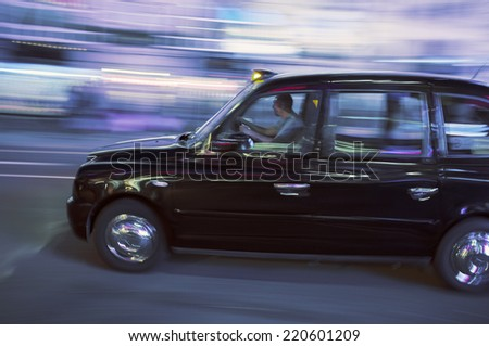 LONDON, UK - APRIL 16, 2014: Blurry image of a London taxi cab moving on a street.