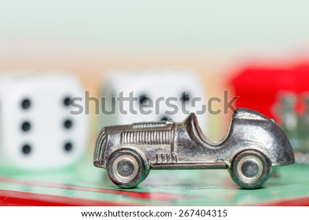 LONDON,UK - APRIL 1,2015 : Car token and dice at the GO space of a monopoly game board - stock photo