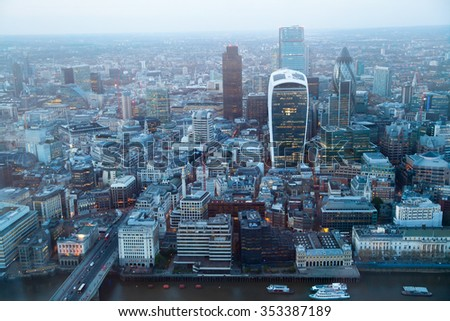 LONDON, UK - APRIL 15, 2015: City of London panorama at sunset. First lights of famous skyscrapers in financial aria - stock photo