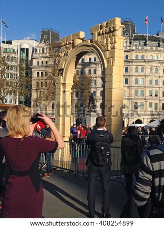 LONDON, UK - APRIL 19, 2016: Crowds photographing a recreation of the Arch of Triumph from Syria's ancient city of Palmyra.  The arch has been recreated by 3D printing and will travel the world.   - stock photo