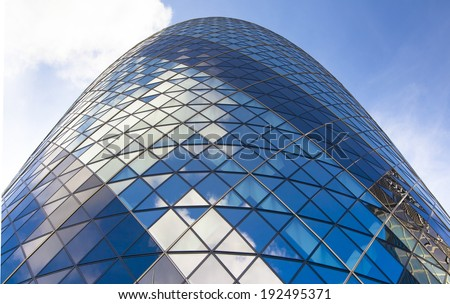 LONDON, UK - APRIL 24, 2014: Gherkin building glass windows texture reflects the sky. The modern glass buildings of the Swiss Re Gherkin, is 180 meters tall, stands in the City of London - stock photo