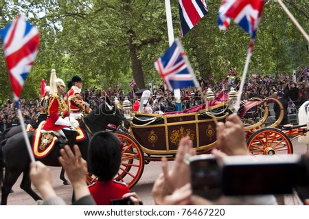 LONDON, UK - APRIL 29: Prince William and Kate Middleton in their carriage on their way to Buckingham Palace after the wedding, April 29, 2011 in London, United Kingdom - stock photo
