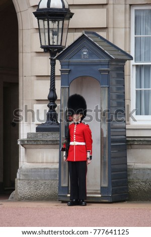 LONDON, UK - APRIL 23, 2016: Queen's Guard soldier stands in front of Buckingham Palace in London, UK. The guards in traditional uniforms are important symbol of the UK.