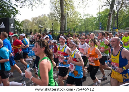 LONDON, UK-APRIL 17: Some of the thousands of runners in the Famous  London Marathon run make their way through the streets in Greenwich on April 17, 2011 in London UK. - stock photo