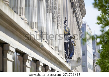 LONDON, UK - APRIL 22: Statue of angel with clock in the facade of famous department store Selfridge & Co., in Oxford Street. April 22, 2015 in London. - stock photo
