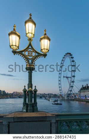 LONDON, UK - APRIL 9, 2014: Street lamp by Thames against London skyline at dusk with the famous London's Eye on background