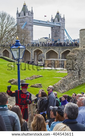 LONDON, UK - APRIL 10TH 2016: A Yeomen Warder talking to visitors during a tour of the historic Tower of London, on 10th April 2016.  Tower Bridge can be spotted in the background. - stock photo