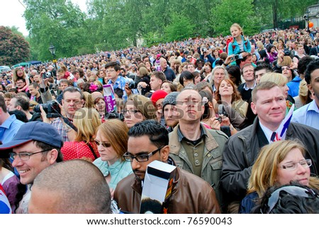 LONDON, UK - APRIL 29: The crowd waiting for the first kiss of the royal couple on the Mall near the Buckingham Palace, April 29, 2011 in London, United Kingdom - stock photo