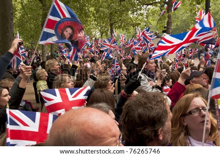 LONDON, UK - APRIL 29: The crowd waving their flags at the wedding of Prince William and Kate Middleton on the Mall, April 29, 2011 in London, United Kingdom - stock photo