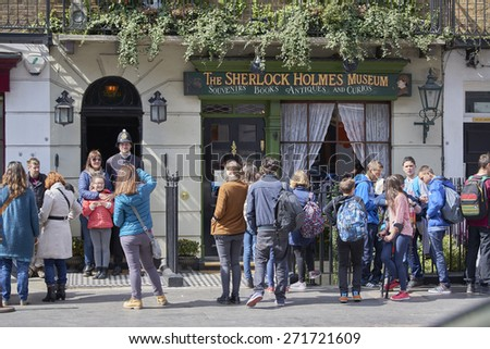 LONDON, UK - APRIL 22: Tourists pose with actor dressed in traditional British police uniform at the entrance of the Sherlock Holmes museum. April 22, 2015 in London. - stock photo