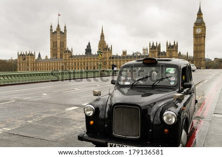 LONDON, UK - APRIL 9, 2012: Typical black London cab on the Westminster Bridge in front of Houses of Parliament. The famous Big Ben is seen on the right of the picture behind the cab. - stock photo