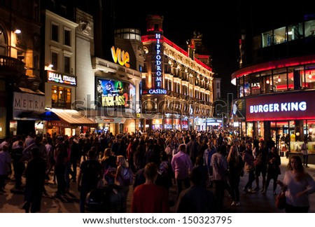 LONDON, UK - AUG 16: people enjoy the nightlife in Leicester Sq in London on August 16, 2013. Leicester Sq is the prime location in London for cinemas and world leading film premiers. - stock photo