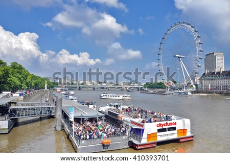 LONDON, UK - AUGUST, 25. Cruise ships on the river Thames on the background of the Ferris wheel London eye on August 25, 2013. United Kingdom.