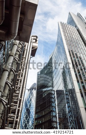 LONDON, UK - AUGUST 21, 2015:  Low angle view of some buildings in the City of London: Lloyds, Willis and Gherkin Tower, designed by Rogers and Foster. London is a major global financial center