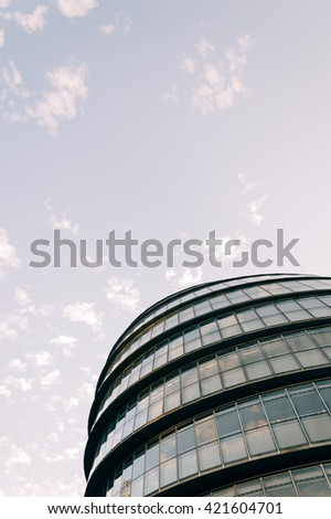 LONDON, UK - AUGUST 21, 2015: Modern office building. Clouds reflections on the glass and detail of a curtain wall. Designed by Norman Foster - stock photo