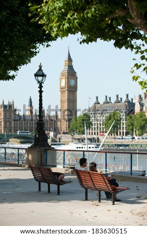 LONDON, UK - AUGUST 19, 2012: people enjoying the beautiful weather in the Southbank area of London, overlooking Big Ben and the Houses of Parliament.  - stock photo