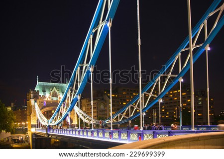 LONDON, UK - AUGUST 11, 2014: Supportive rails Tower bridge on the river Thames in night lights - stock photo