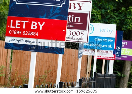 """London, UK-circa 2013: Estate agent """"let by"""" signs line the road in a suburb of London - stock photo"""
