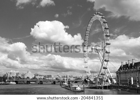 LONDON, UK / CIRCA JULY 2014 - The famous London Eye and the Thames river, two of London's most iconic landmarks seen on a bright summer day - stock photo