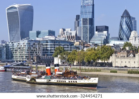 London, UK, 02/10/2015 : Daytime City of London view of skyscraper office buildings, Tower of London river walkway, Thames river bus pier and tourists on WAVERLEY ship, sea going paddle steamer - stock photo