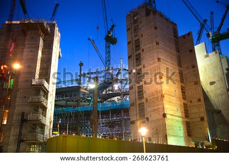 LONDON, UK - DECEMBER 19, 2014: Building site with cranes in the City of London business. New development next to bank of England. Night view - stock photo