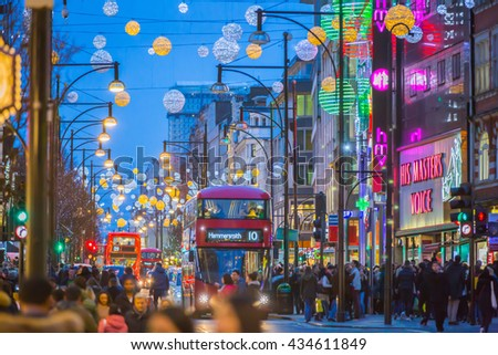 LONDON, UK - DECEMBER 30, 2015: Christmas lights decoration at Oxford street and lots of people walking during the Christmas sale, public transport, buses and taxies - stock photo