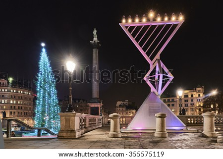 LONDON, UK - DECEMBER 19: Night shot of Menorah next to Christmas tree in Trafalgar Square, set up for Chanukah. December 19, 2015 in London. - stock photo