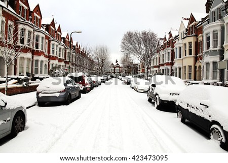 London, UK, December 18 2010 - Snow winter cityscape of a terraced street in Kilburn with blizzard conditions showing cars covered with ice and snow - stock photo