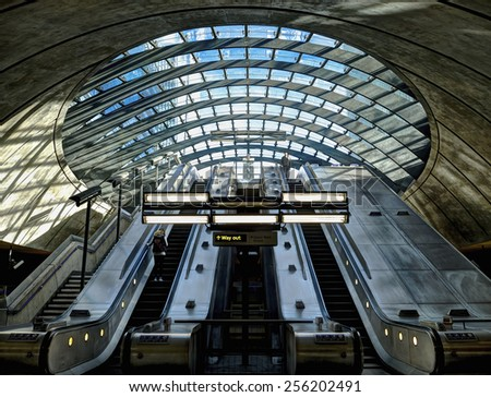 LONDON, UK - February 8, 2014: Interior shot of Canary Wharf Underground Station. The usually busy underground station on a quiet Saturday morning with two unidentified travellers on the escalators. - stock photo