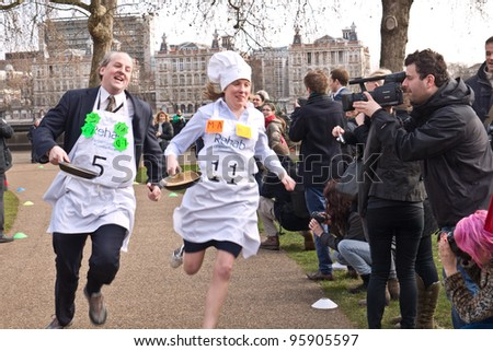 LONDON,UK-FEBRUARY 21: Lord Redesdale (left) and MP Tracey Crouch race past the crowds  in the 2012 Parliamentary Pancake Race, out side the Houses of Parliament on February 21, 2012 in London, UK - stock photo
