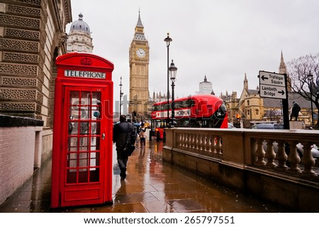 London, UK-FEBRUARY 12: Traditional red telephone box in the rainy day with the Big Ben and red bus in the background on February 12, 2014 in London, UK. Horizontal orientation.