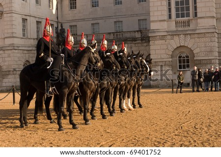 LONDON, UK- JANUARY 19: Members of the Queen's Royal Horse Guards, the Blues and Royals Regiment,outside Horse Guards Parade, during the Changing of the Guard Ceremony. January 19, 2011 in London, UK. - stock photo