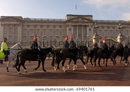 LONDON, UK-JANUARY 19: Members of the Queen's Royal Horse Guards, the Blues and Royals Regiment, ride past Buckingham Palace, after the Changing of the Guards Ceremony, January 19, 2011 in London, UK. - stock photo