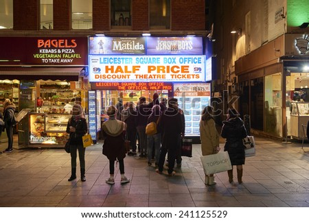 LONDON, UK - JANUARY 02: People lined up for discounted theatre tickets at night in Leicester Square. January 02, 2015 in London. - stock photo