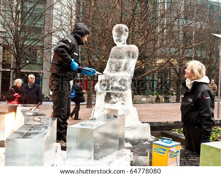 LONDON, UK - JANUARY 15: Team Members Work on Their Ice Sculpture for the Annual London Ice Sculpture Festival Competition, Canary Wharf. London, January 15 2010 - stock photo