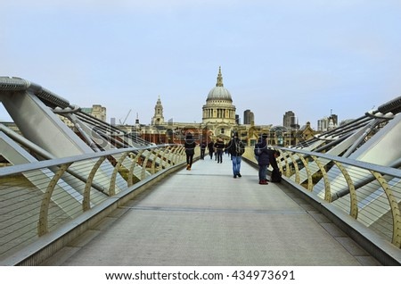LONDON, UK - JANUARY 17: Unidentified people on Millennium bridge with St. Paul's cathedral behind, on January 17, 2016 in London, England