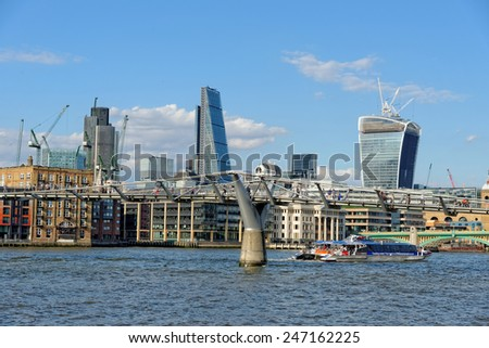 LONDON, UK - JULY 1, 2014: A City Cruises tour boat is approaching the Millennium bridge on the Thames river. The bridge is linking the City of London with the South Bank. - stock photo