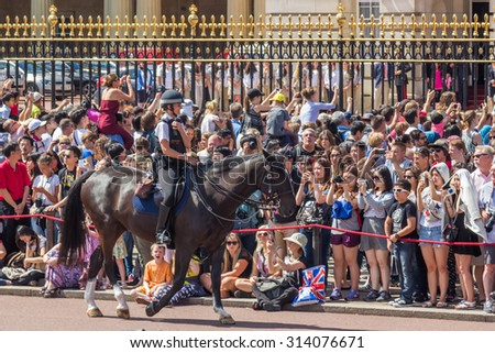LONDON, UK - JULY 21, 2015: A female police officer on a horse controlling crowds in front of Buckingham palace in London, England. - stock photo