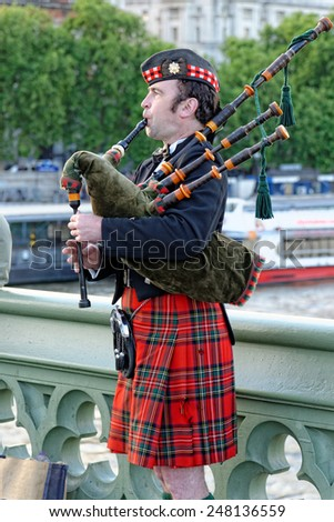 LONDON, UK - JULY 1, 2014: Bagpiper musician on Westminster Bridge in a traditional Scottish costume. - stock photo