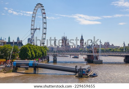 LONDON, UK - 22 JULY, 2014: Centre of London view from the London bridge. Big Ben, Parliament, London eye and passing boats on river Thames - stock photo