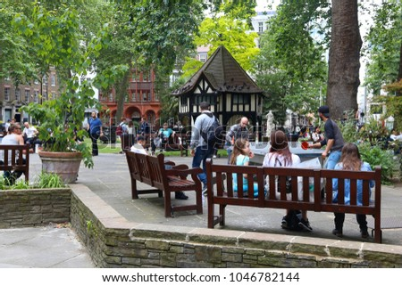 LONDON, UK - JULY 9, 2016: People visit the park at Soho Square in London, UK. London is the most populous city in the UK with 13 million people living in its metro area.