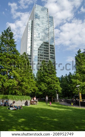 LONDON, UK - JULY 1, 2014:  Sunbathers enjoying the greenery of Jubilee Park in London's Docklands overlooked by the gleaming headquarters of international law group Clifford Chance. - stock photo