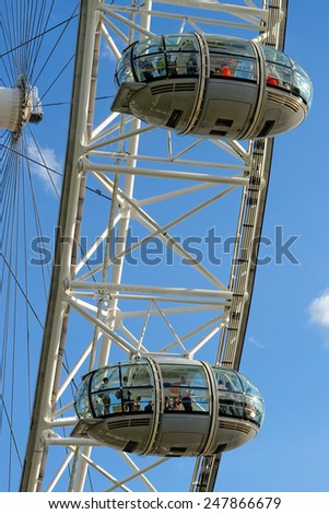 LONDON, UK - JULY 1, 2014: Tourists enjoy the view over the city in the capsules of the London Eye, Europe's tallest Ferris wheel on the South Bank of the River Thames, a famous tourist attraction. - stock photo