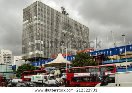 LONDON, UK  JUNE 16, 2014:  Busy traffic outside the dilapidated Elephant and Castle Shopping Centre in Southwark, South London. - stock photo