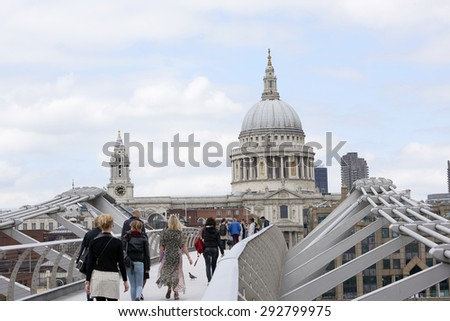 LONDON, UK - JUNE 23: Dome of Saint Paul's cathedral, with people crossing Millennium Bridge in the foreground. June 23, 2015 in London.