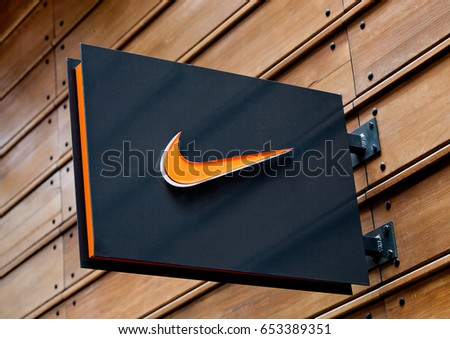 LONDON, UK - JUNE 02, 2017: Nike logo on black display plate on wooden background. Nike, Inc. is an American corporation  manufacturing of footwear, apparel, equipment, accessories and services