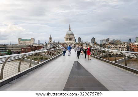 London, UK - June 17, 2015: People crossing the Millennium Bridge. The bridge alignment is such that a view of St Paul's south facade is presented from across the river, framed by the bridge supports.