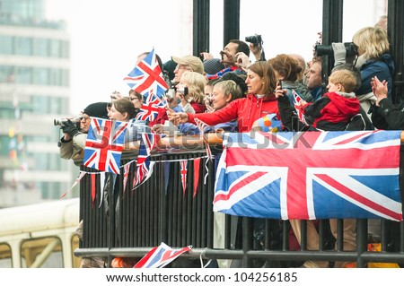 LONDON, UK - JUNE 3:  Rainy day flag waving and photography by the public during the Queen Elizabeth II Diamond Jubilee celebrations in London, UK on June 3, 2012 - stock photo